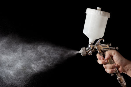 Photo pour Close up of a spray paint gun with black background - image libre de droit