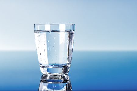 Photo pour Drinking water in glass on blue - image libre de droit