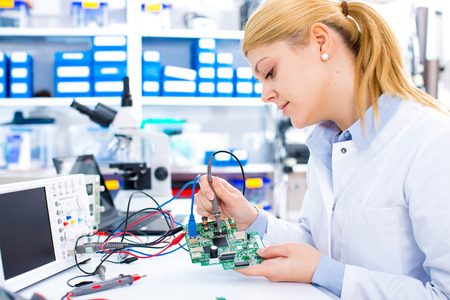 Photo for Engineer working with circuits. A woman engineer solders circuits sitting at a table.  Microchip production factory. Technological process. Assembling the PCB board.  Girl repairing electronic device on the circuit board.  - Royalty Free Image