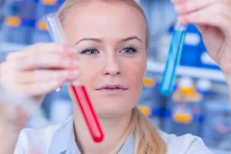 Photo pour Female laboratory assistant with chemical experiment in scientific laboratory. Female medical or scientific researcher using test tube on laboratory. - image libre de droit