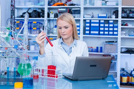 Photo pour Girl laboratory Assistant works with an antiviral drug in a pharmaceutical laboratory - image libre de droit