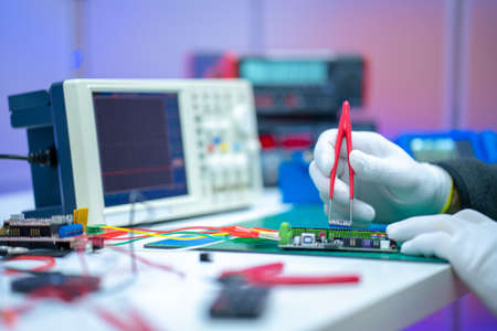 Photo for Development of electronic devices in the modern electronics laboratory, on a table, microprocessor oscilloscope and multimeter - Royalty Free Image