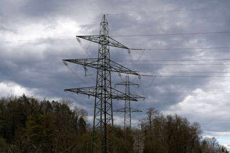Photo pour High voltage pylons for transfer of electricity in woodland of dicdeous trees in early spring, in village Birmensdorf. There is a dramatic cloudy sky on the background and a lot of copy space. - image libre de droit