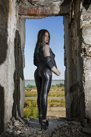 Young girl wearing leather jacket and pants posing in an old building
