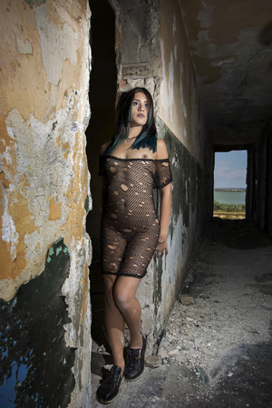 Young girl posing in a black fishnet dress
