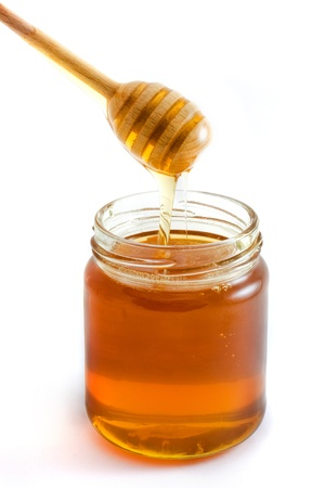Honey dripping into jar isolated over white