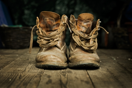 Pair of old worn boots on wooden floor boards