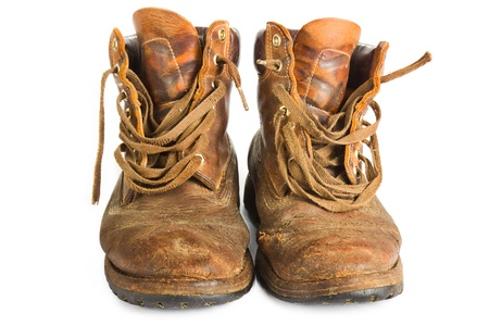 Pair of old worn brown leather work boots on white