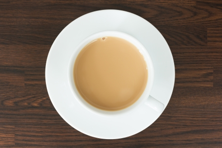 Overhead view of tea in a cup and saucer on a wooden worktop