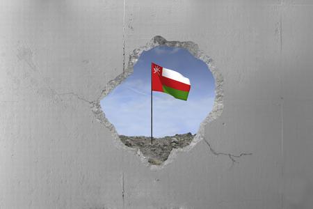 Oman flag behind a concrete wall.