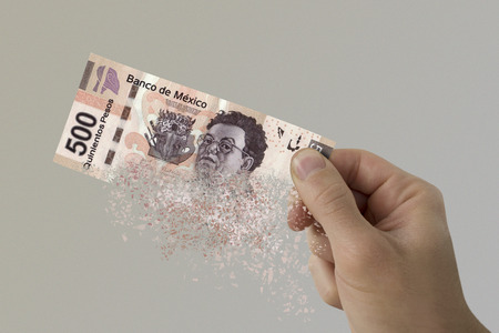Five hundred Mexican Pesos bill pulverizes in a man's hand.