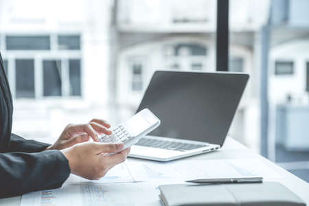 Photo pour businesswomen bookkeeper use calculator and laptop doing account for paying tax on white desk in working office. - image libre de droit