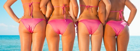 Photo pour four girls in bikini from behind posing on beach - image libre de droit