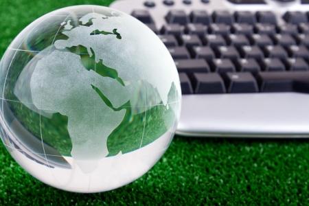 Foto de keyboard and glass globe on green grass - Imagen libre de derechos