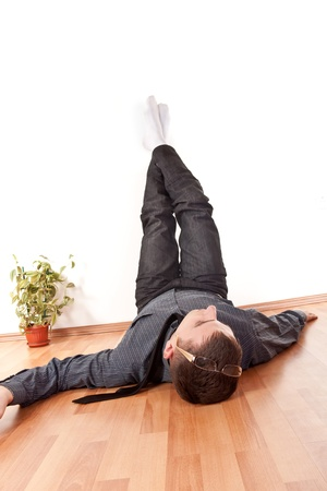 businessman relaxing with his legs up  on wall at home