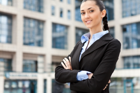 young and attractive businesswoman in suit , image is taken outdoors on a street