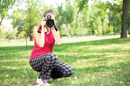 beautiful young woman with camera on nature