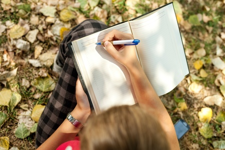 Photo pour  girl sitting outdoor and writing , top view - image libre de droit