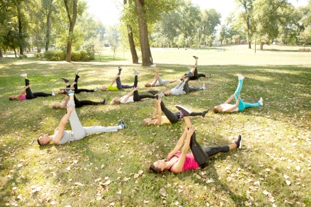 Photo pour large group of people lying on grass and stretching, outdoor - image libre de droit