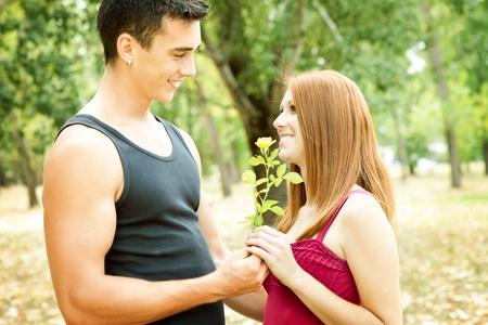 Foto de young romantic couple with flower, outdoor - Imagen libre de derechos