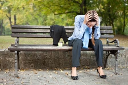 worried caucasian businesswoman sitting on bench in park