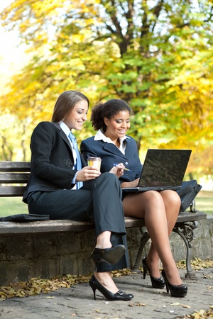 two businesswomen working on laptop, sitting on bench in park