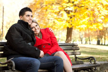 young affectionate couple embracing in park in autumn