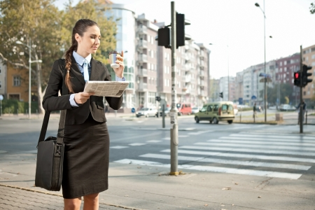 young businesswoman drinking coffee on street