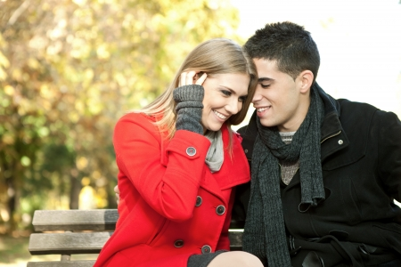 love couple on  sitting on bench, young man whispers to his girlfriend