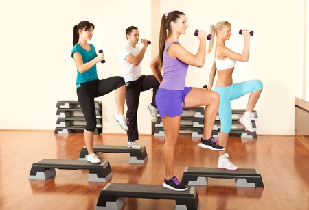 Group of people at the gym exercising with free weights