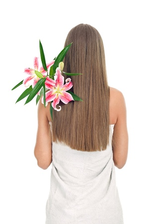 woman back covered with long hair and a bunch of fresh pink lily on shoulder, concept- femininity