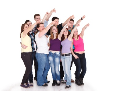 Large group of cheerful students pointing at copy space on white background