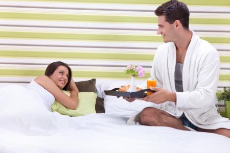 Man serving women a romantic breakfast in bed.