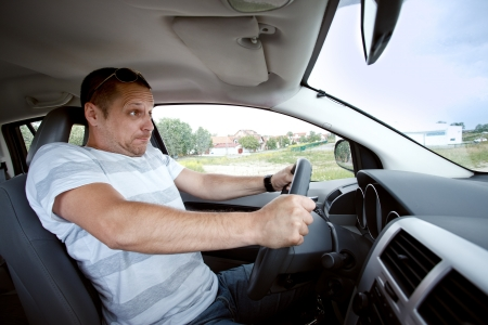 Scared man driving car very fast,  focused on the driver's face