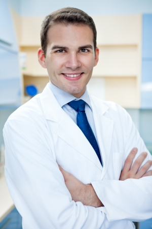 portrait of young handsome success doctor with arms crossed