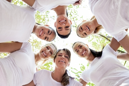 Group of women standing in the circle, smiling at the camera, low angle view