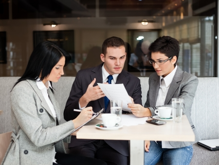Young business people working over a paperwork and drinking coffee