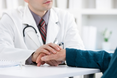 Doctor holding patient's hand, helping hand concept