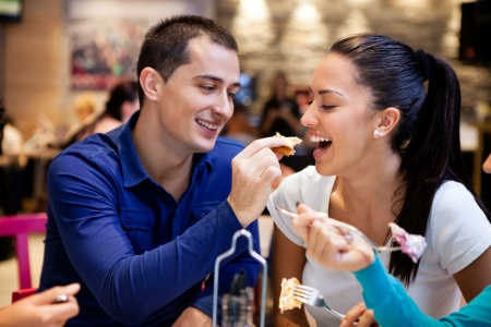 Happy young couple eating lunch restaurant