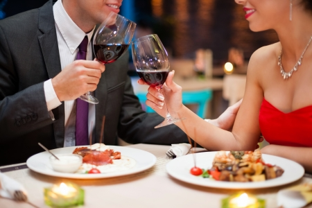 Hand holding a glass with red wine and toasting, celebration