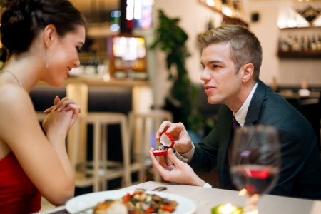 Photo for Man proposing to his girlfriend while they are having a romantic date at the restaurant - Royalty Free Image