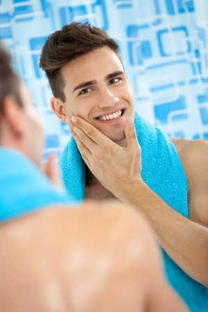 Young men touching his soft cheek after shaving