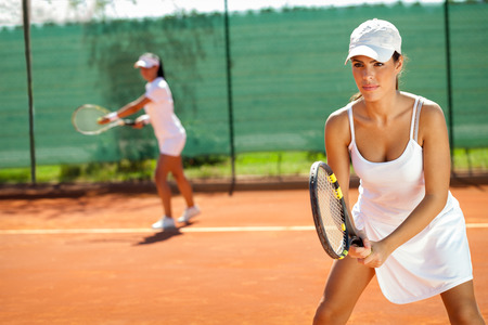 young women playing doubles at tennis at the tennis court