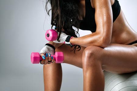 Foto de  Sweaty female body after exercise sitting on fitness ball  - Imagen libre de derechos