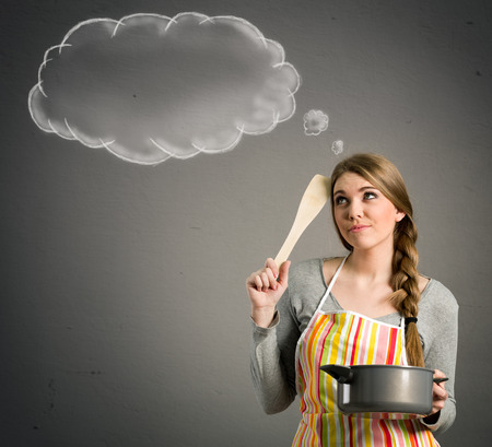 young beautiful housewife with empty think clouds, concept - What to cook today?