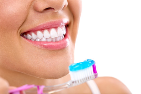 Photo pour Smiling young woman with healthy teeth holding a tooth-brush - image libre de droit