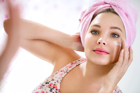 Photo for Young girl front of mirror in bathroom putting cream on her face - Royalty Free Image