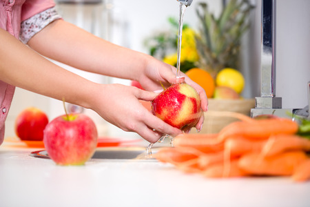 Photo for Woman hands washing tasty apple under the tap - Royalty Free Image