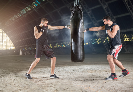 Two boxers hitting the sandbag