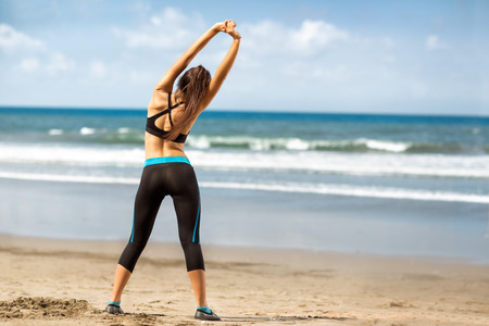 Fitness woman exercising and stretching arms on beautiful summer day